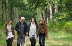Mother and father enjoying a walk through the woods with daughters. Portrait of a mother and father enjoying a walk through the woods with daughters Royalty Free Stock Photo