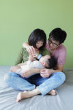 A mother and father feeding their baby bottle stock image