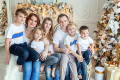 Mother father and five children near Christmas tree at home stock photography