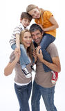 Mother and father giving children piggyback ride Stock Image