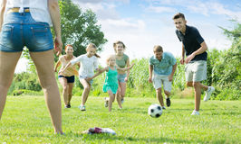 Mother and father with glad kids running in park Royalty Free Stock Photo