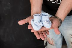 Father Hands Holding blue Newborn Baby Booties.Expectation for a baby. Mens hands with small shoes for unborn baby stock images