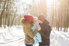 Mother and father holding their baby boy and kissing his outside in the winter Stock Photo