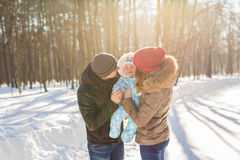 Mother and father holding their baby boy and kissing his outside in the winter Stock Image