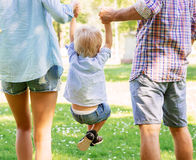 Mother and father holding their son in the park. Mother and father holding their son in the air in the summer garden Royalty Free Stock Photography