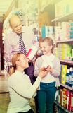 Mother and father with kid picking in pharmaceutical store Royalty Free Stock Photo