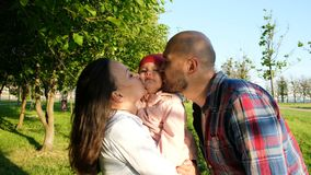 Parents kiss the child on both cheeks. Happy young family having a rest on nature in a park at sunset stock image