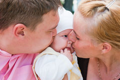 Mother and father kissing baby Royalty Free Stock Image