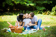 Mother and father kissing daughter. Family having picnic on a park meadow. Kissing stock photos