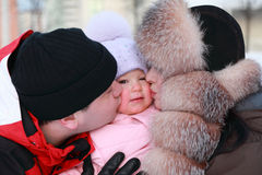 Mother and father kissing daughter, winter. Mother and father kissing his little daughter, winter, multistore building, focus on girl Royalty Free Stock Photography