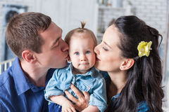 Mother and father kissing his year-old daughter. Lovely family together at home. Mother and father kissing his year-old daughter Stock Photo