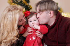 Mother and father kissing their baby girl Stock Images
