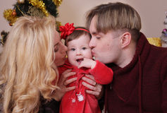 Mother and father kissing their baby girl Stock Photos