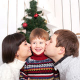 Mother and father kissing their kid. In the morning Christmas Eve. Homemade Christmas and happy family concept Stock Images