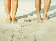mother and father legs with small baby shoes Royalty Free Stock Photo