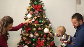 Mother, father and little baby decorated christmas tree. Man holding child near fir tree, showing bright decoration. Happy family celebrates Christmas together stock footage