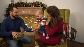 Mother, father and little baby sitting in the room with christmas decoration. The man gives small present box to the. Mother, father and little baby are in the stock footage