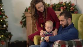 Mother, father and little baby are in the room with christmas decoration. Man holding little son on his laps, woman. Bends and kisses her husband, both smiling stock video