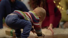 Mother, father and little baby sitting on the floor in the room with christmas decoration. Little child trying to walk. On beige fluffy carpet. Mom and dad stock footage