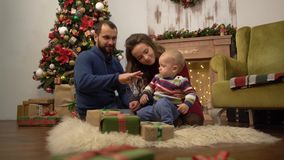 Mother, father and little baby sitting on the floor in the room with christmas decoration. Dad playing with child stock footage