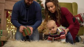 Mother, father and little baby sitting on the floor in the room with christmas decoration. Man gives small present box. Mother, father and little baby sitting on stock footage