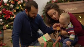 Mother, father and little baby sitting on the floor in the room with christmas decoration. Man gives small present box. Mother, father and little baby sitting on stock video