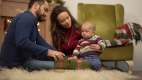 Mother, father and little baby sitting on the floor in the room with christmas decoration. Man gives small present box. Mother, father and little baby sitting on stock video footage