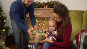 Mother, father and little baby sitting near decorated christmas tree. Dad present box to the child sitting on mother. Laps. Happy family celebrating Christmas stock video