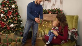 Mother, father and little baby sitting near decorated christmas tree. Man taking small present box and gives to the. Mother, father and little baby sitting near stock footage
