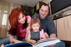 Mother, father and little daughter reads book royalty free stock image