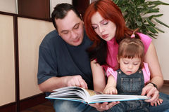 Mother, father and little daughter reads book Royalty Free Stock Images