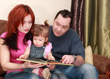 Mother, father and little daughter reads book Stock Photography