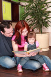 Mother, father and little daughter reads book stock images