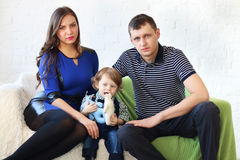 Mother, father and little son sit on couch Stock Photo