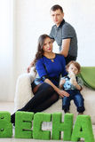 Mother, father and little son sit on white couch Stock Photography