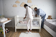 Mother And Father Looking At Baby Daughter In Nursery Cot royalty free stock images