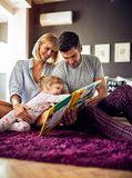 Mother and father looking puzzle book with child royalty free stock photo