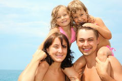 Mother and father near water with two little girls Royalty Free Stock Photo