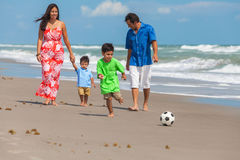 Mother Father Parents Boy Children Family Beach Football Soccer. A happy family of mother, father parents & two boy son children, playng football or soccer and Stock Photography