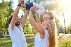 Mother and father play with the child in the park in the summer. Stock Photo