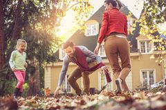 Mother and father playing with daughter backyard. Mother and father playing with daughter. Autumn season. Happy family Royalty Free Stock Image