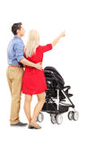 Mother and father pushing a baby stroller Royalty Free Stock Photography