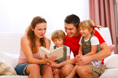 Mother and father reading to daughters. Mother and father reading to twins daughters Stock Image