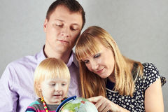 Mother with father show a  globe to small blond daughter on a gr Royalty Free Stock Image