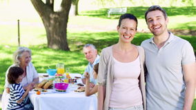 Mother and father smiling at camera with family behind them eating lunch Royalty Free Stock Images