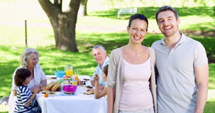 Mother and father smiling at camera with family behind them eating lunch stock footage