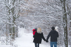 Mother, father, son, daughter walk on a winter forest. Stock Photos
