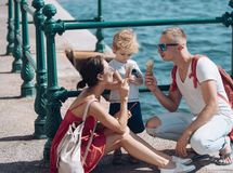 Mother and father with son eat ice cream at sea. Summer vacation of happy family. Child with father and mother. Family stock photo
