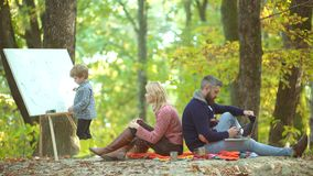 Mother and father with son having fun outdoor. Romantic couple. Cheerful family having picnic. Happy child artist. Drawing picture on autumn nature stock footage