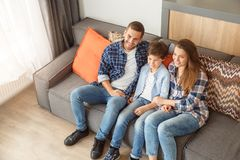 Family at home sitting on sofa in living room together hugging watching tv happy top view stock photography